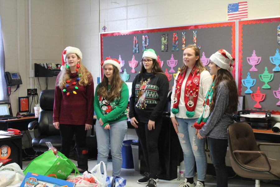 In+honor+of+the+holiday+season%2C+chorus+students+Kayla+Smith%2C+Emma+Henderson%2C+Diana+Agne%2C+Kayla+Anderson+and+Trinity+Klock+deck+out+in+holiday-themed+outfits+and+accessories.+Going+from+door+to+door%2C+they+spread+the+holiday+spirit+as+they+perform+Christmas+songs+in+front+of+students+and+teachers.+