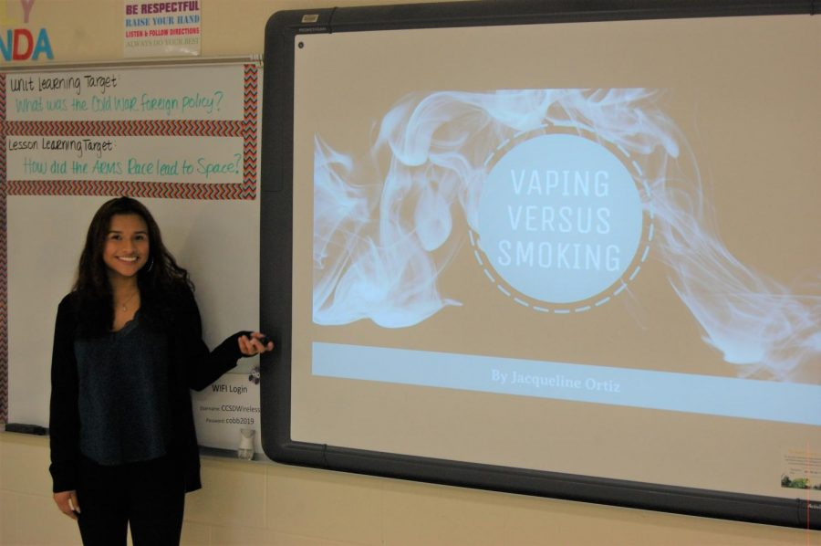 Magnet+senior+Jacqueline+Ortiz+delivers+her+research+presentation%2C+titled+%E2%80%9CVaping+versus+Cigarette+Smoking%3A+Generational+Perspectives.%E2%80%9D+After+years+of+focused+instruction%2C+these+seniors+used+their+developed+researching+skills+to+study+a+modern+topic+of+their+choosing.+Using+collected+data+and+graphs+to+visually+represent+their+information%2C+all+the+presentations+featured+a+minimum+12-minute+discussion+and+post+questioning.