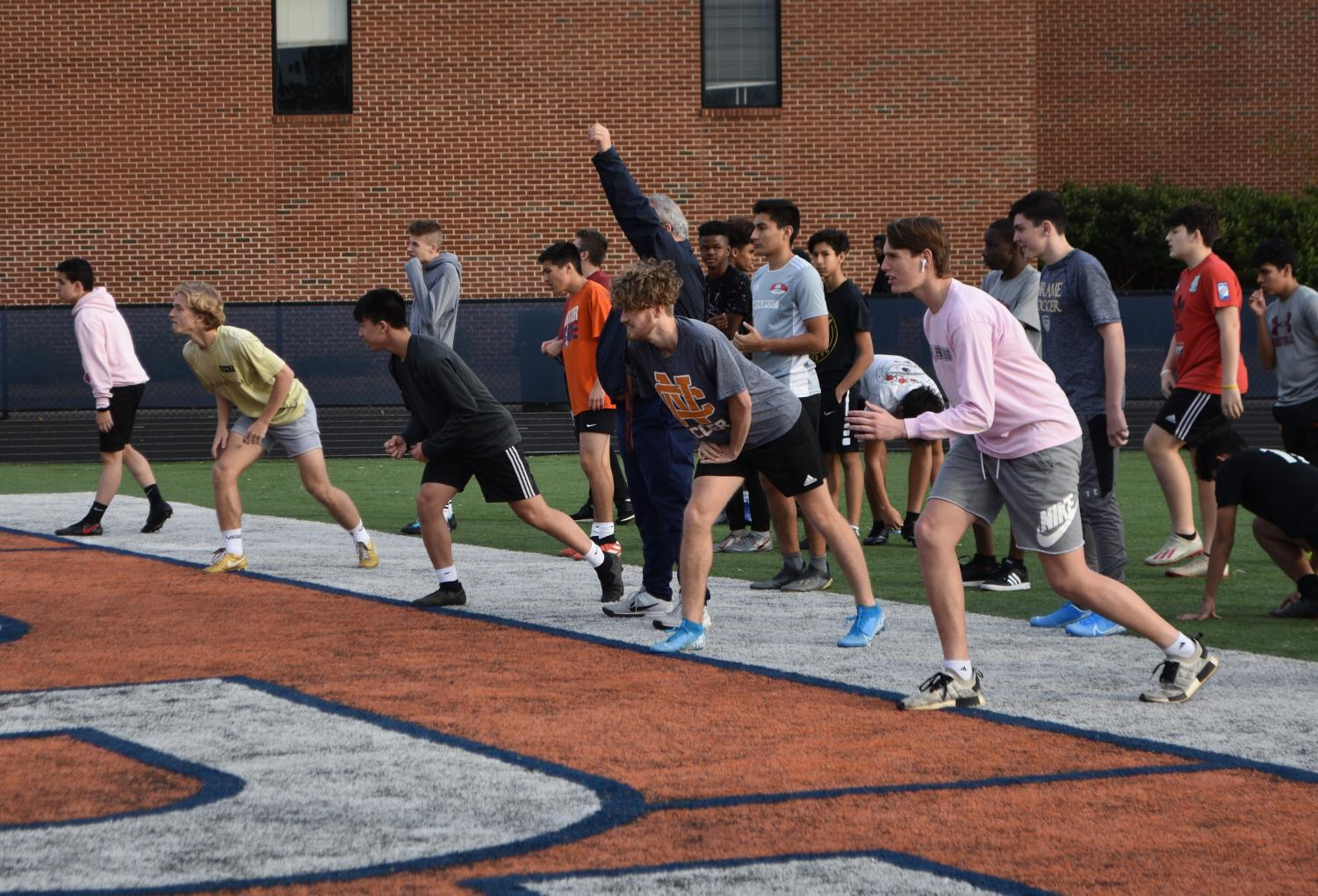 """Conditioning consisted of a variety of drills that focused on building endurance and improving physical agility. """"These drills allow the coaches to see each player's strengths and weaknesses,"""" senior Zoe Kemp said. Players prepared to run 50-yard sprints as Varsity boys Head Coach Panell observed."""