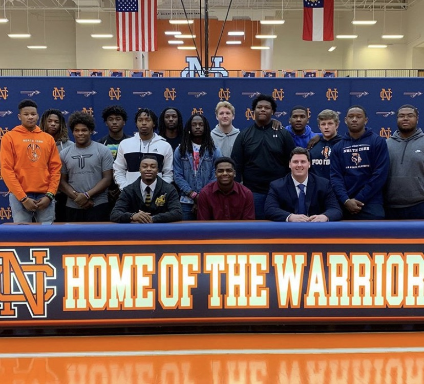 NC+Varsity+football+players+%28pictured+left+to+right%29+Malik+Washington%2C+Kalen+Carver+and+Joshua+Kimmons+wear+colors+that+represent+the+universities+they+officially+signed+to.+Their+football+team+surrounds+and+support+the+seniors+as+they+begin+preparing+to+take+the+next+step+to+further+their+career.+