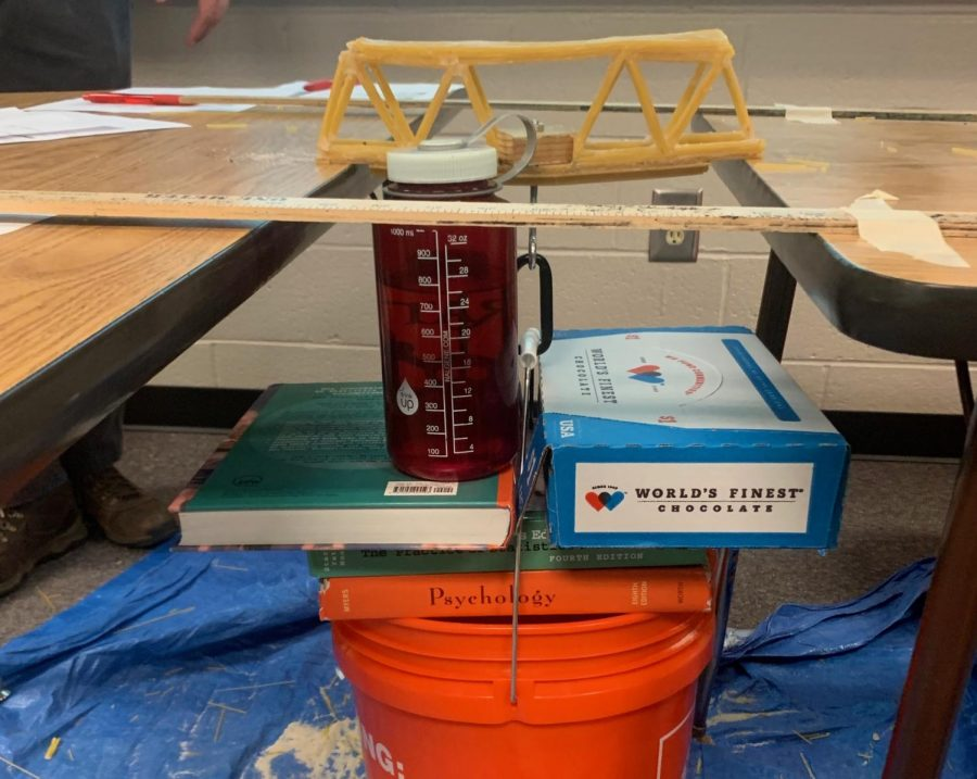 "Honors geometry students across the school united this week to construct bridges using strictly uncooked spaghetti noodles and elmers glue. This project created challenges for many students forcing them to use their problem solving skills while incorporating what they have learned within the geometry classroom. NC sophomore Tyler Rogers overcame the challenge and constructed a bridge that held 72.8 pounds before collapsing. ""I enjoyed this project. It was definitely a challenge, but in the end it was worth it when my bridge held the most weight and beat the school record,"" Rogers said."