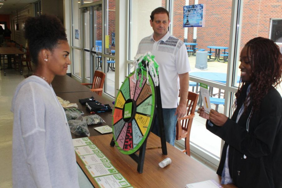 The program Teens in the Driver's Seat spreads driver safety and awareness in the cafeteria today. Students come up and answer a question about safety for a chance to spin the wheel and earn prizes such as t-shirts, bracelets, rings, and bumper stickers. The program aims to keep teen drivers aware of the dangers of the road while educating them on how to drive cautiously.