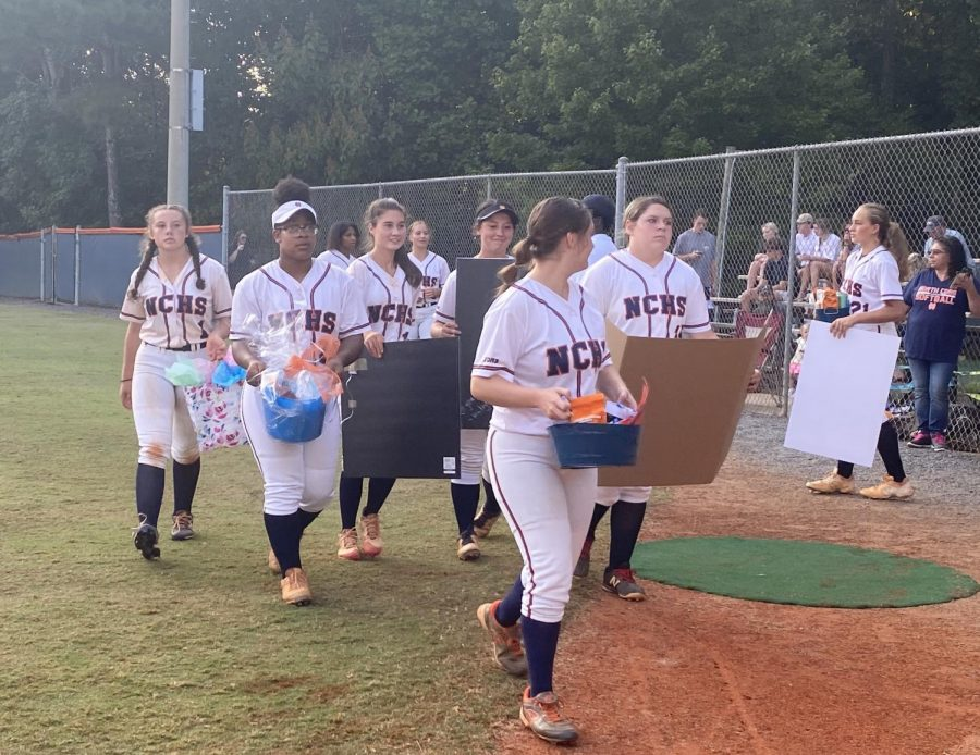 Like a photo captured straight out of a coming-of-age film, the NC Varsity Softball team pictured prepared to spread love on their Senior Night. Underclassmen walked onto the field, hands filled with goodie baskets and posters they made to give to each of the seniors during their ceremony. The girls went on to win their game, the final score a (9-7).