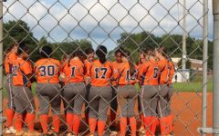 """The NC Lady Warrior softball team huddle around 3rd base and pray before and after each game, followed by a chant to lift their spirits. """"Praying and just talking to each other before each game gets us excited to go play. It kinda relieves some of the pressure we're under,"""" junior Mackenzie Ogburn said."""