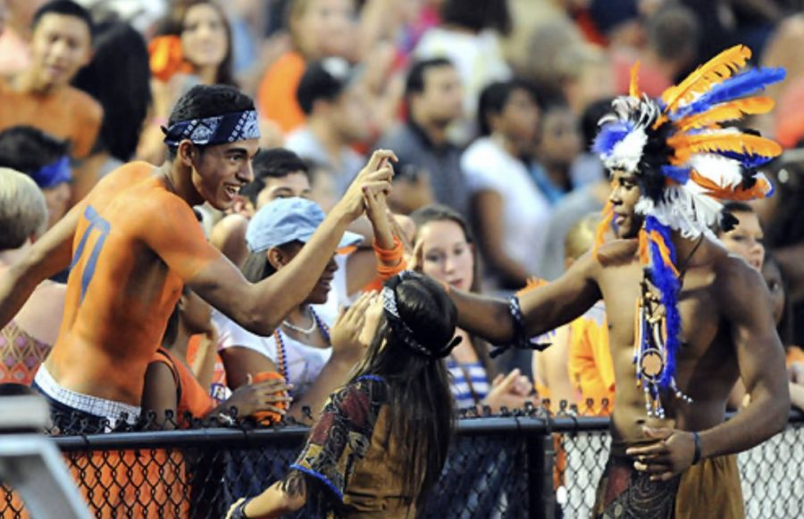 Neil Shah (left) gives a high five to NC mascot Kyle Ford during a break in the North Cobb-Alpharetta game Friday, August 26, 2011. Until recently, a NC student, working with the athletic department and cheerleaders, wore Native American costumes at football games.
