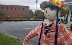 "A scarecrow stands in downtown Kennesaw as part of the Scarecrows on Main event, and while Halloween draws ever closer, families look for Covid-safe activities to celebrate the holiday. ""Halloween is my favorite holiday, and I was feeling a little concerned that this year we might have to skip on it. Luckily our community is coming together to make sure Covid doesn't put a damper on celebrations,"" Kennesaw Mountain sophomore John Davis said."